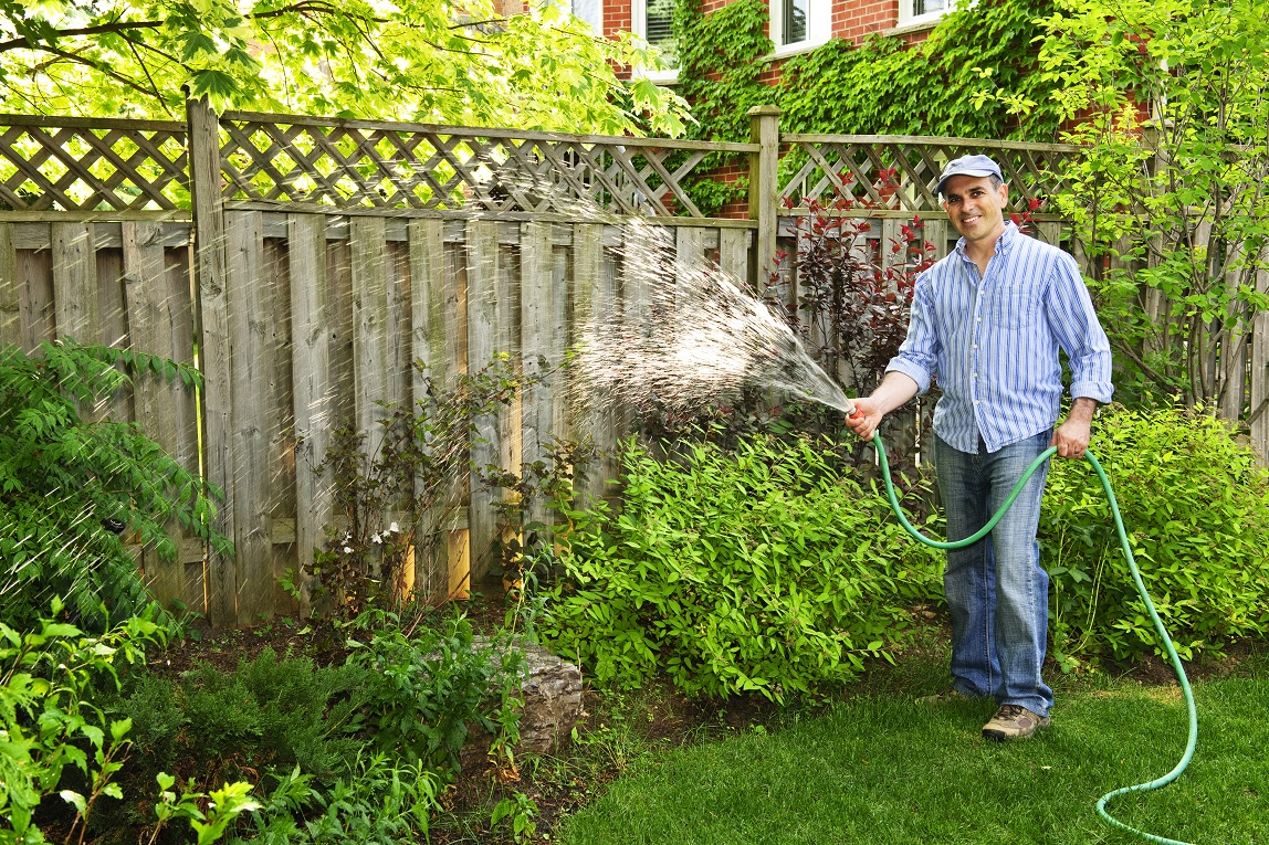 man watering garden and lawn