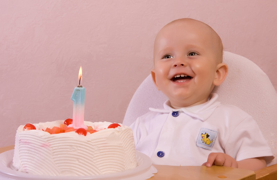 Adorable little boy on his first birthday with cake